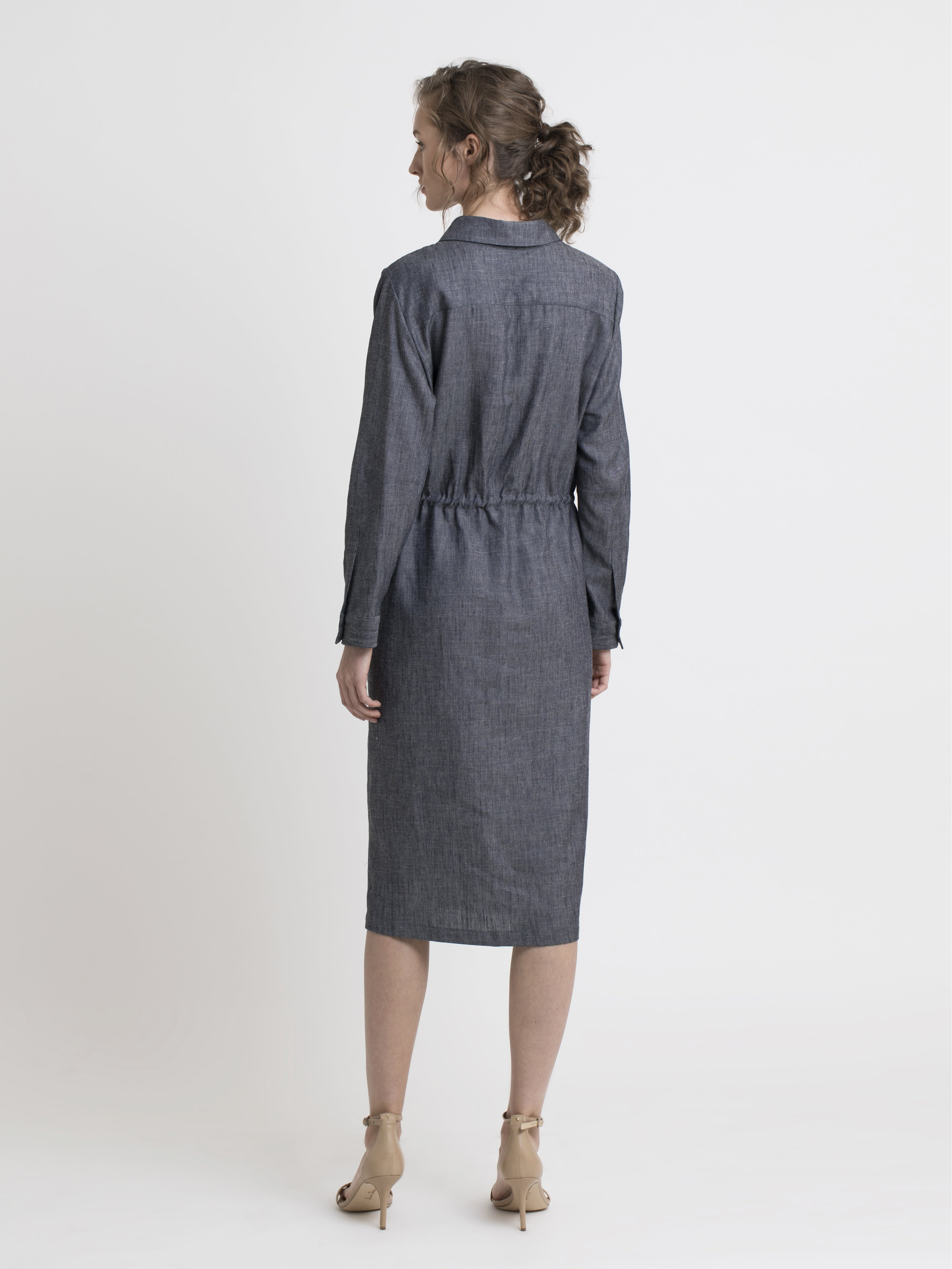 Back view of a female model wearing a knee length long sleeve straight cut denim shirt dress with drawstring inserted belt and high heel nude sandals. From the RÉZO women's collection.