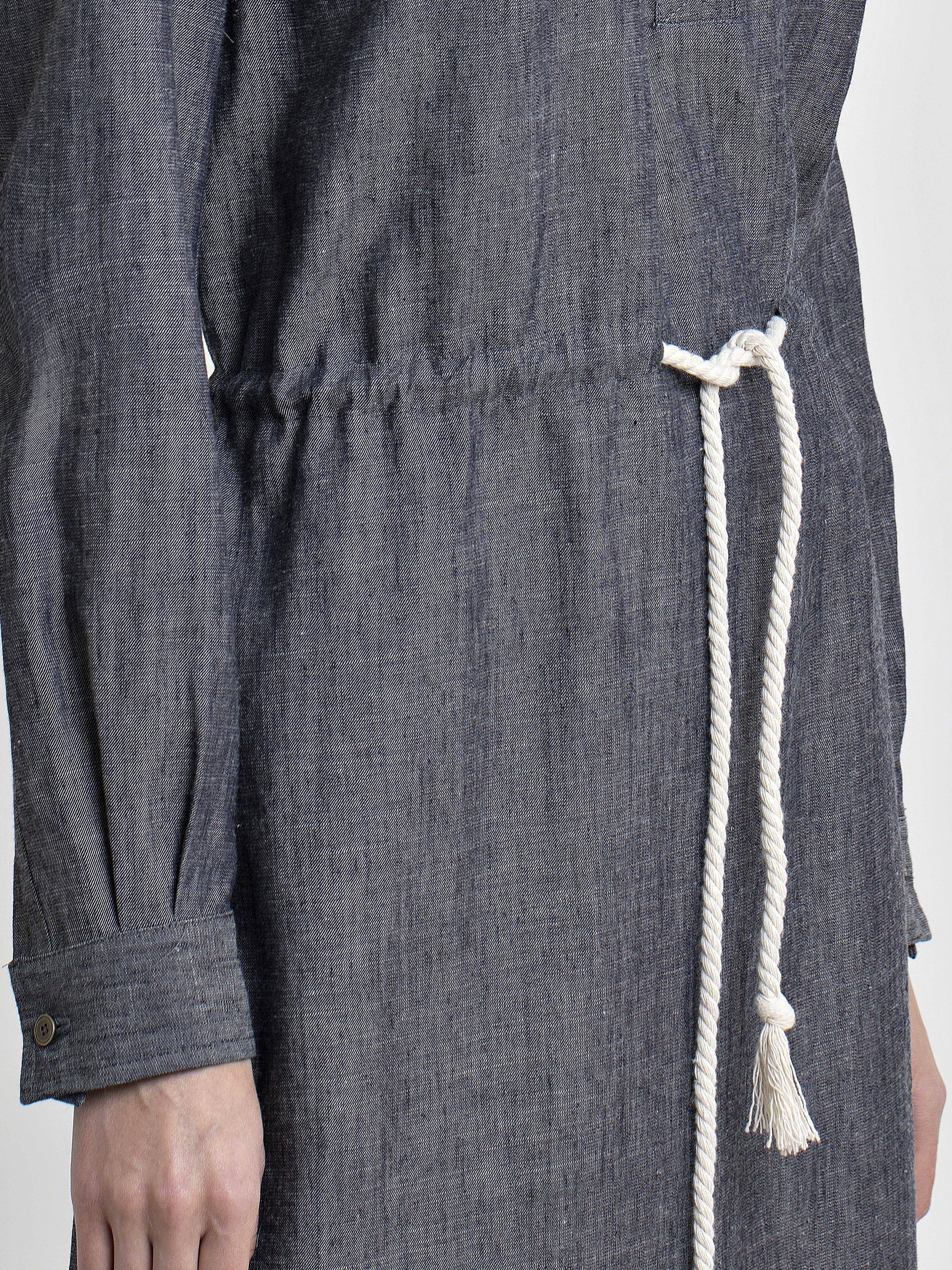 Waist close up view of a female model wearing long sleeve straight cut denim dress with drawstring inserted belt. From the RÉZO women's collection.