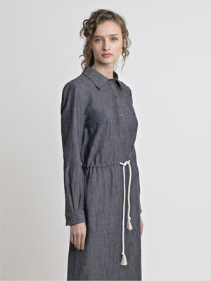 3/4 view of a female model wearing long sleeve straight cut denim shirt dress with drawstring inserted belt. From the RÉZO women's collection.