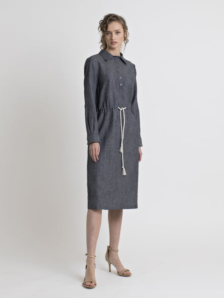 Full view of a female model wearing a knee length long sleeve straight cut denim shirt dress with drawstring inserted belt and high heel nude sandals. From the RÉZO women's collection.