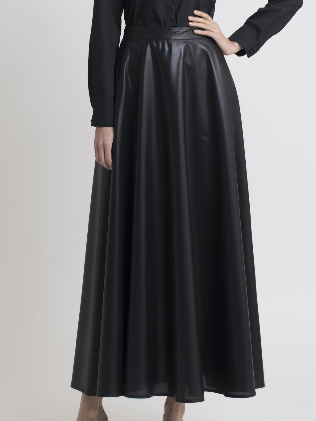 Lower body view of a female model wearing a black cotton dress shirt, and a long eggshell-gloss black flared skirt, from the RÉZO women's collection.