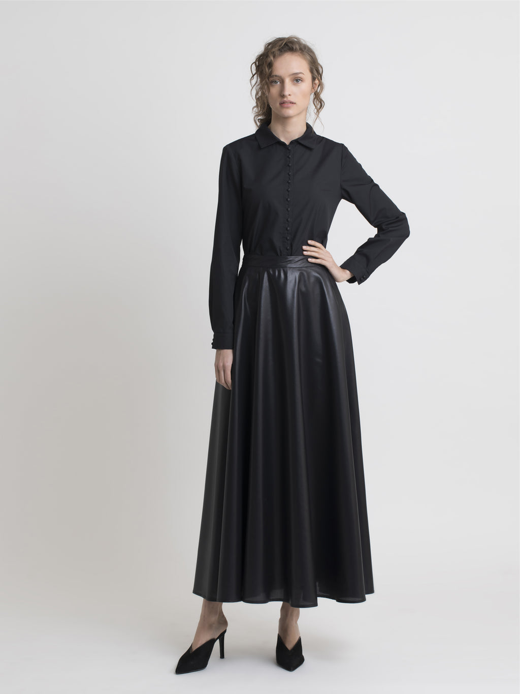 Full front view of a female model wearing high heels slip on black shoes, a black cotton dress shirt, and a long eggshell-gloss black flared skirt, from the RÉZO women's collection.