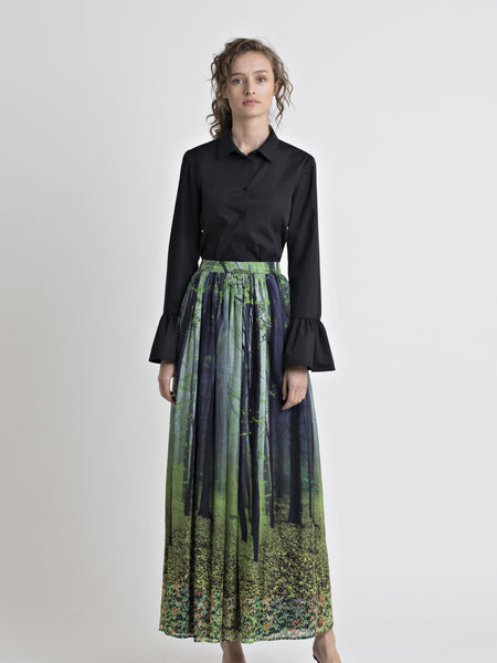 Full front view of a female model wearing a black cotton flared cuff dress shirt, and a long cotton forest print gathered skirt, from the RÉZO women's collection.