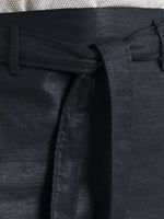close up hip view of a shiny navy pencil skirt with belt loops and a tie belt, from the RÉZO women's collection.
