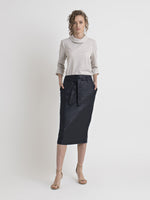 Full front view of a female model wearing high heel nude color sandals, a white-sand raised collar 3/4 sleeve top, and a below the knee shiny navy pencil skirt with pockets, belt loops and a tie belt. From the RÉZO women's collection.