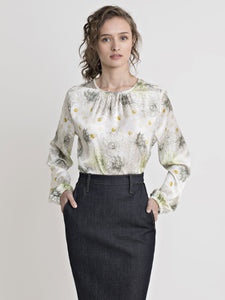 Front view of a female model wearing a dark blue denim pencil skirt with side pockets, and an off white gathered neckline top with an olive-mustard feafy-dot print, and long elastic-gathered cuff sleeves. From the RÉZO women's collection.