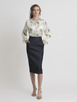 Front view of a female model wearing nude color high heel sandals, a dark blue denim pencil skirt with side pockets, and an off white gathered neckline top with an olive-mustard feafy-dot print, and long elastic-gathered cuff sleeves. From the RÉZO women's collection.