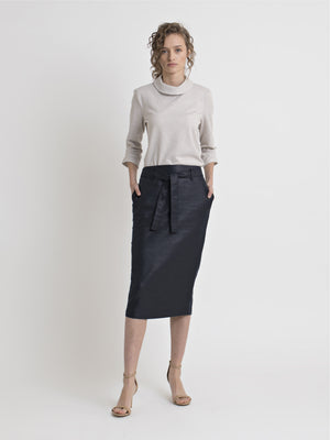 Front view of a female model wearing nude color high heel sandals, a shiny navy below the knee pencil skirt with pockets, belt loops and a tie belt, with a tucked in raised collar - 3/4 sleeve - off-white terry blouse with coffee circle pattern. From the RÉZO women's collection.