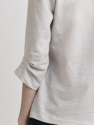 Back left torso view of a female model wearing an off white terry blouse with coffee color circle pattern and a dart  detail on the 3/4 sleeve edge. From the RÉZO women's collection.