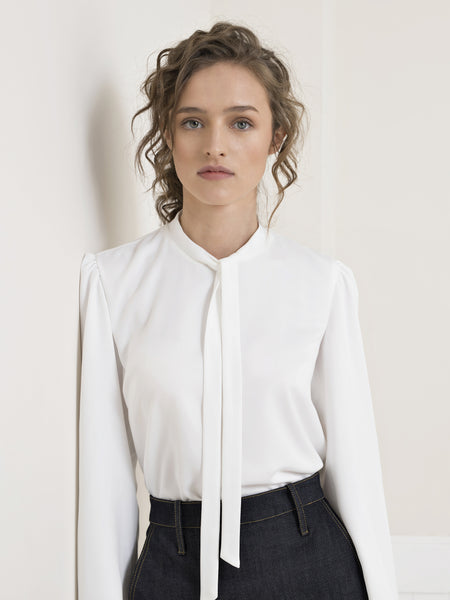 Upper body view of a female model wearing a dark blue denim pencil skirt, with a tucked in long sleeve, tie neck, white crepe blouse. From the RÉZO women's collection.