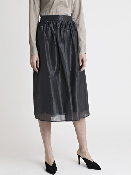 Lower body front view of a female model wearing a sand color dress shirt, black high heel slip on shoes, and a below the knee glossy black gathered skirt, from the RÉZO women's collection.