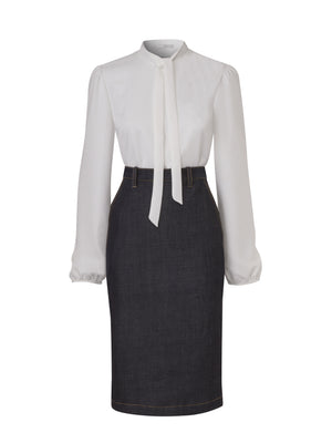 Front view of a dark blue denim, below the knee pencil skirt, with a tucked in long sleeve, tie neck, white crepe blouse. From the RÉZO women's collection.