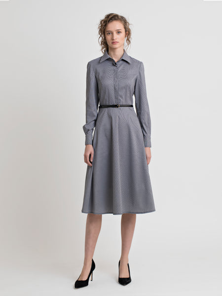 Front view of a female model, wearing high heel black shoes, and a semi fitted black and white check shirt dress, with covered placket and a patent leather black narrow belt. From the RÉZO women's collection.