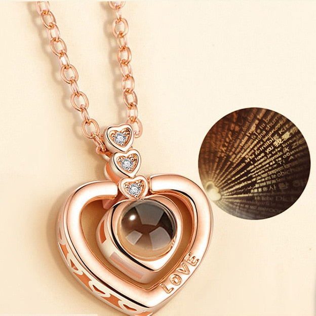 memory of love hearts necklace rose gold with I love you in 100 different languages projection