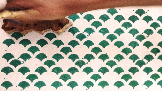 Blockprinting the kamal lotus print in green dye on white fabric