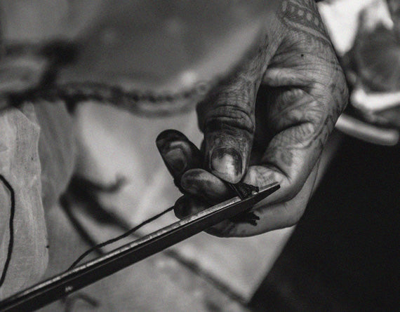 Hands of an artisan working with thread