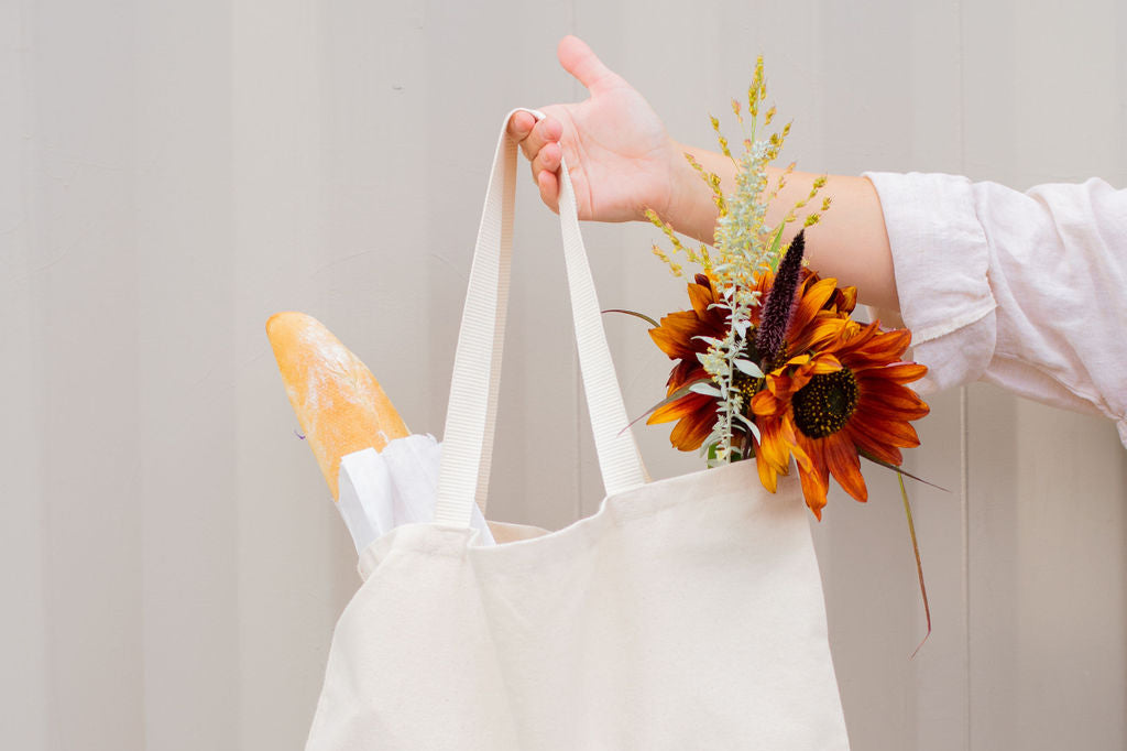 woman arm holding reusable grocery bag with baguette and flowers in it
