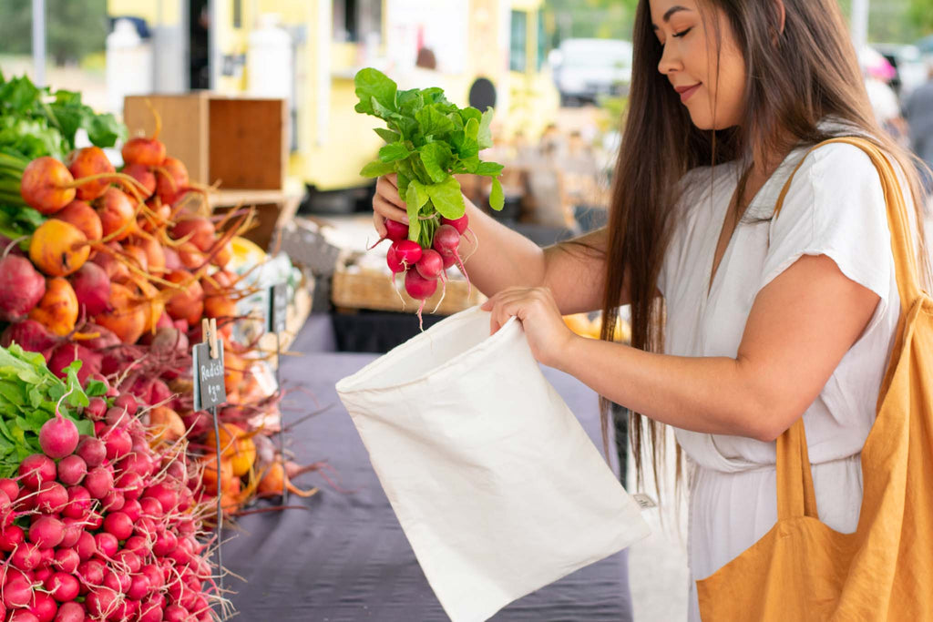 woman putting radishes into reusable cotton produce bag at farmers market