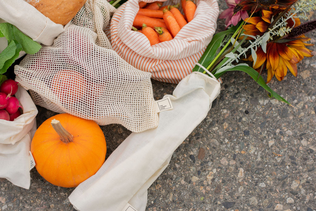 carrots, pumpkin, and flowers in reusable bags on the ground