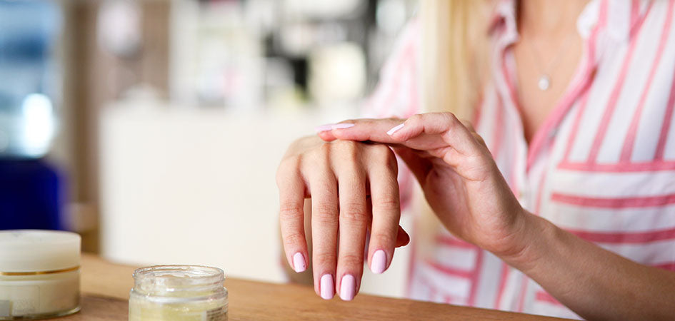 Woman rubbing cbd balm on her hands. where to buy cbd topical creams.