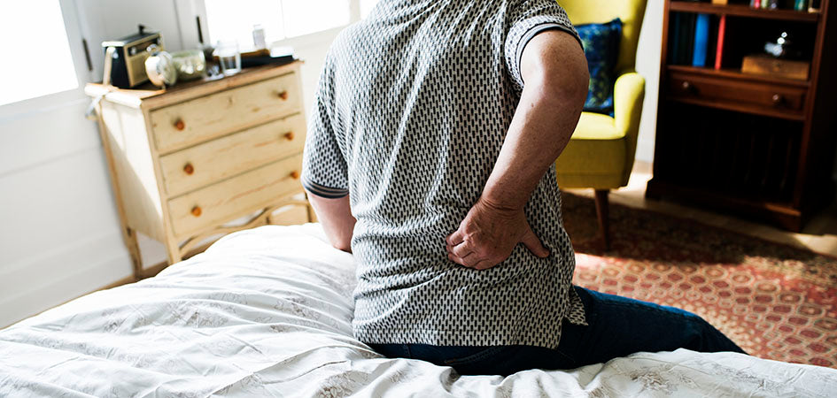 Man showing signs for lower back pain in the morning. cbd oil for chronic back pain. How to use cbd oil for pain. Will cbd oil help back pain? Does cbd oil help with back pain?