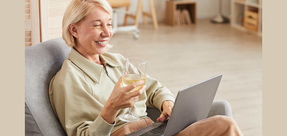 Elderly woman smiling having a glass of wine. full spectrum cbd oil for sale. cbd oil for anxiety for sale.