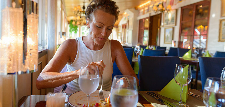 Woman eating at a restaurant. cbd balm for back pain. Does cbd balm work for pain?