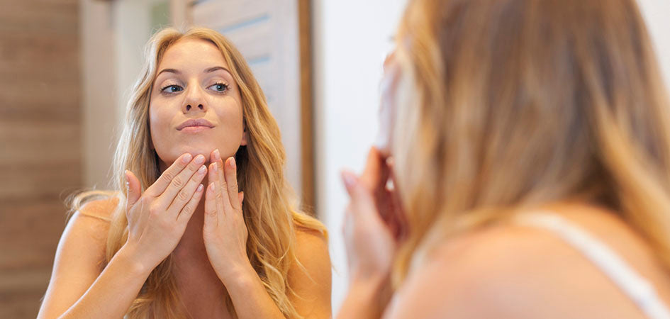 Woman touching her face looking in the mirror. pure cbd oil for pain relief.