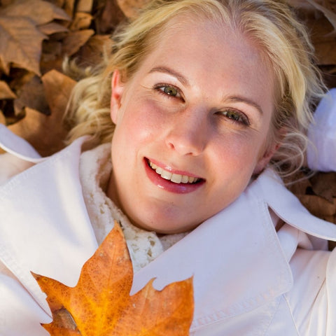 blond woman with fall leaf, glowing fall skincare