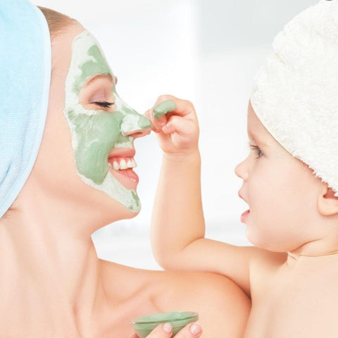 Mother and baby, mom with green face mask that child is playing with