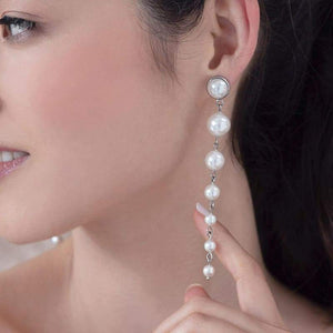 Silver Caiti modern pearl drop earrings from left