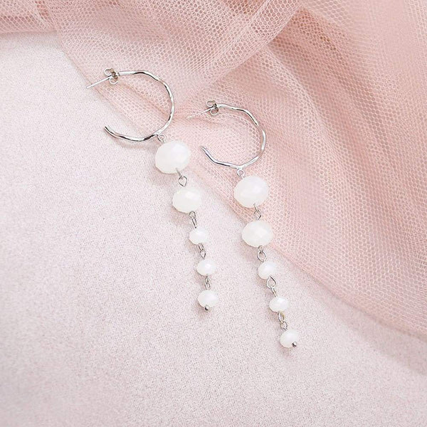 White Kelana Dangle Bead Earrings on pink