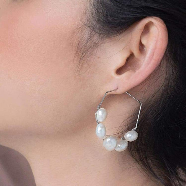 Kygo freshwater pearl geo earrings on left ear