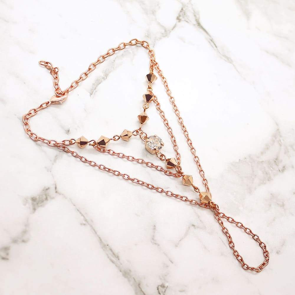 Rose gold Ryda bohemian hand chain on grey