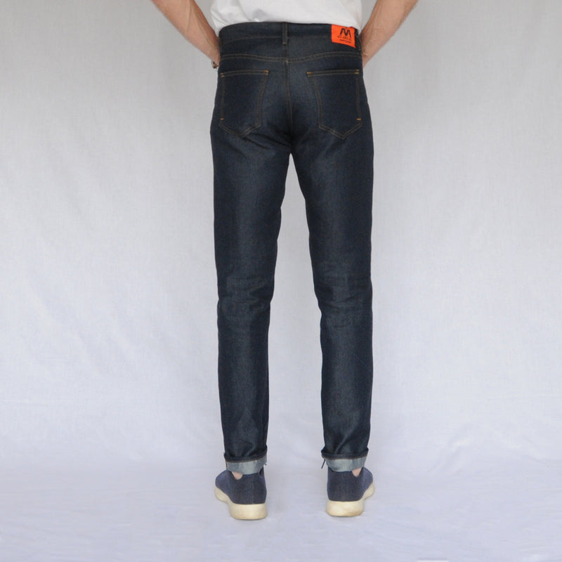 on model image of back of again&again dark wash, slim-fit jeans. Model is wearing a white shirt and blue Allbirds