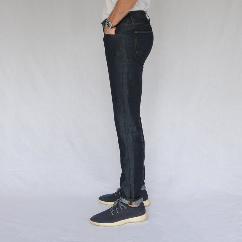 on model image of left side of again&again dark wash, slim-fit jeans. Model is wearing a white shirt and blue Allbirds