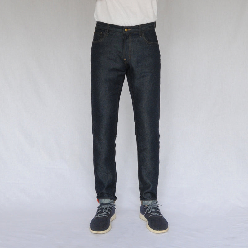 on model image of front of again&again dark wash, slim-fit jeans.  Model is wearing a white shirt and blue Allbirds