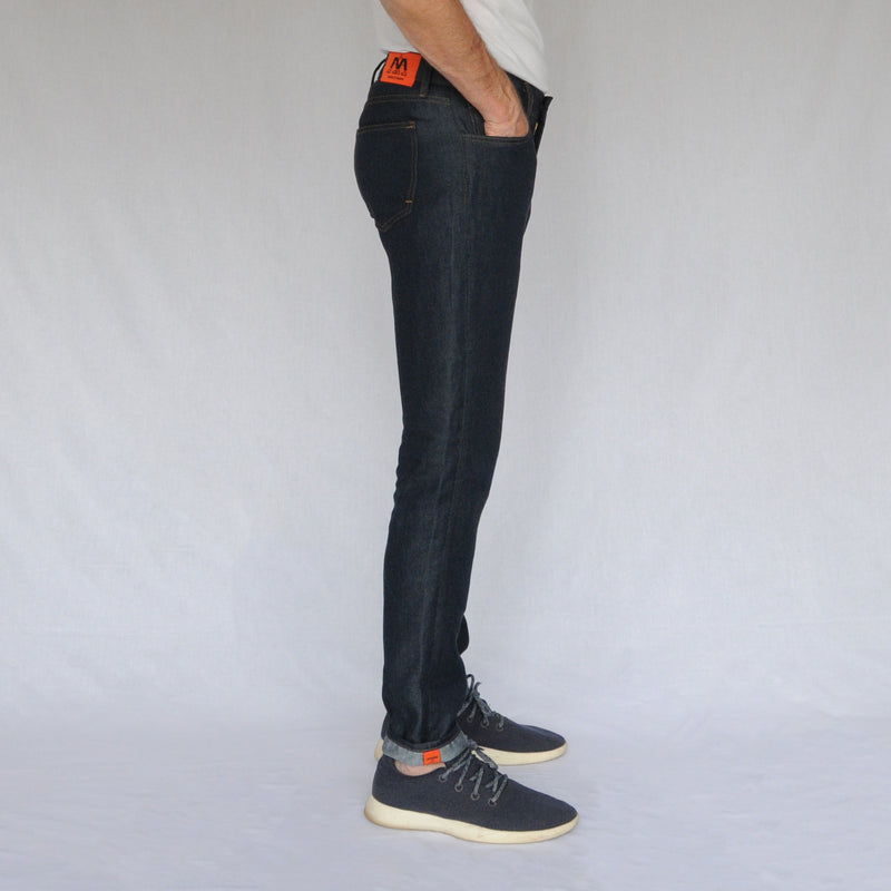 on model image of right side of again&again dark wash, slim-fit jeans. Model is wearing a white shirt and blue Allbirds