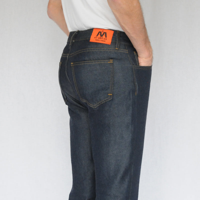 close up on model image of back of again&again dark wash, slim-fit jeans. Model is wearing a white shirt.