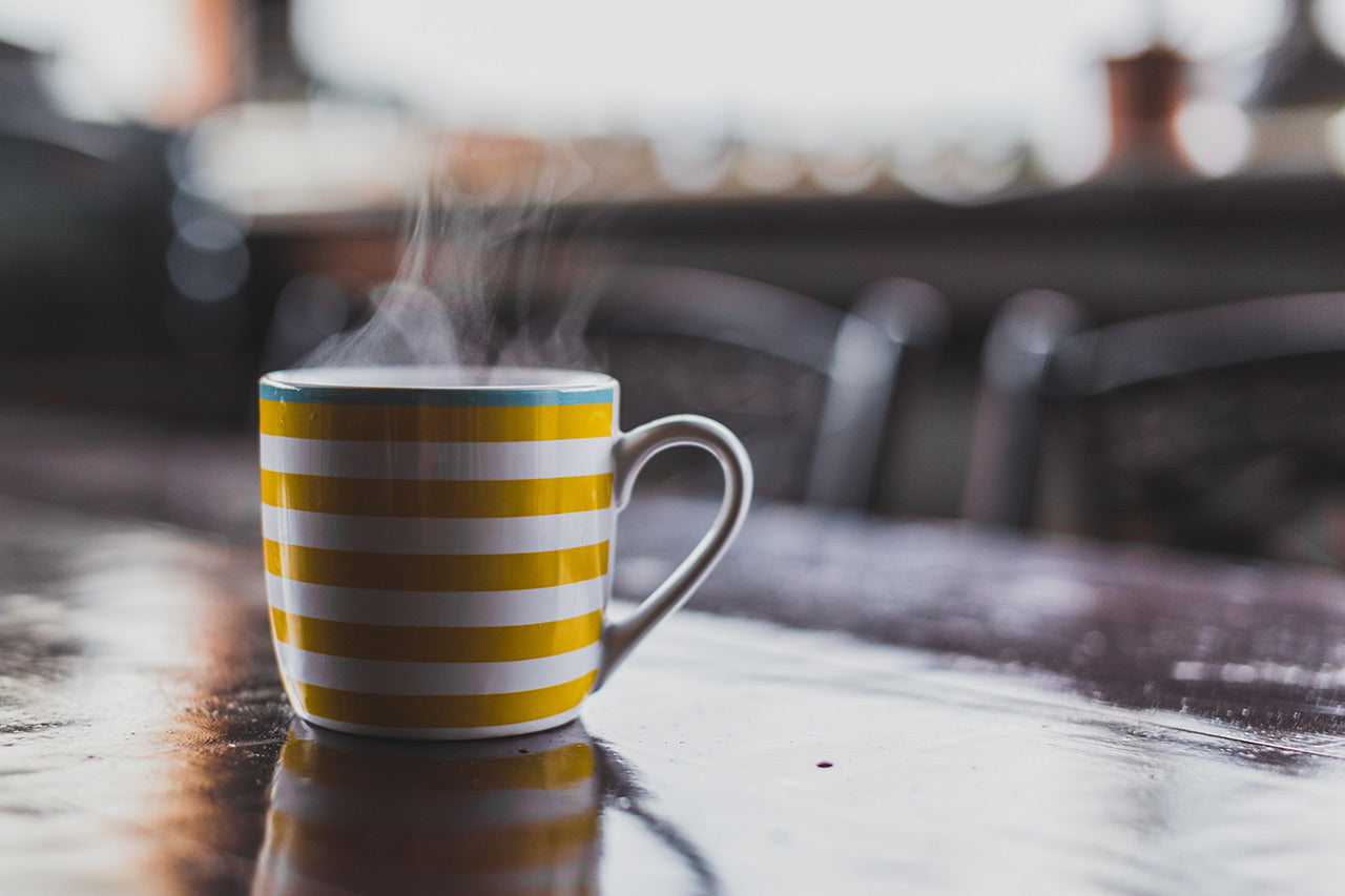 Yellow and white stripy mug with steam on kitchen table.