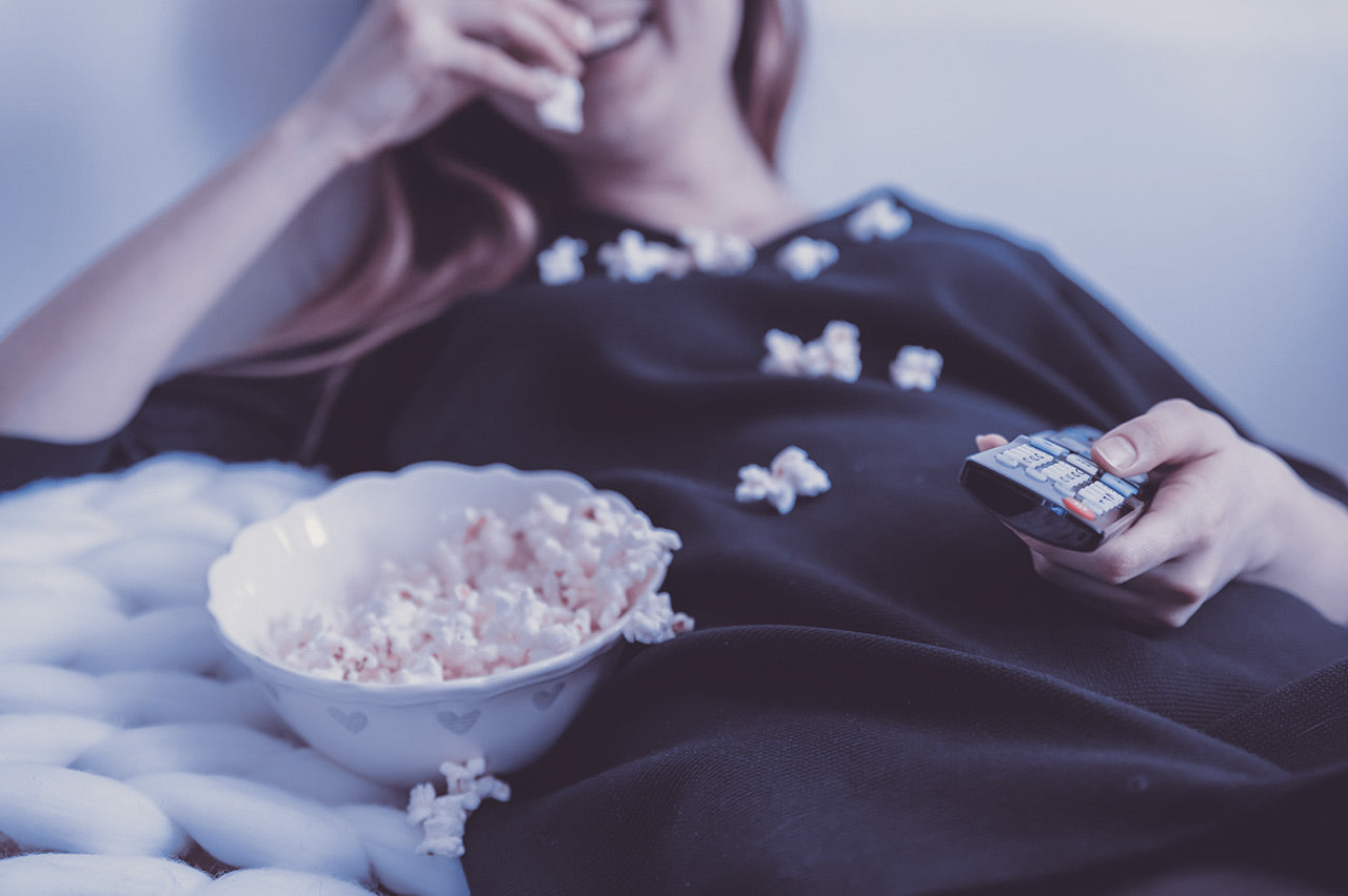 Happy woman watching TV and eats popcorn at night.