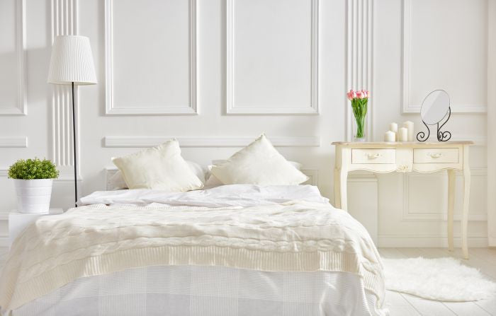Fresh bed linen in white bedroom during spring time.