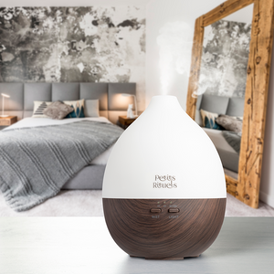 Essential oil diffuser with a dark wooden base and white top.