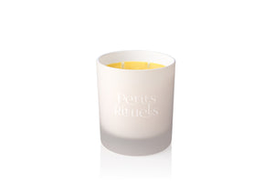 Orange scented candle in white Petits Rituels glass.