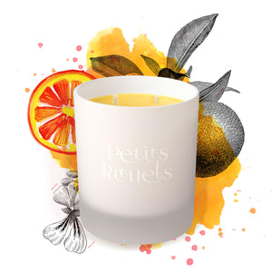 Orange scented candle with floral illustrations of oranges in background.