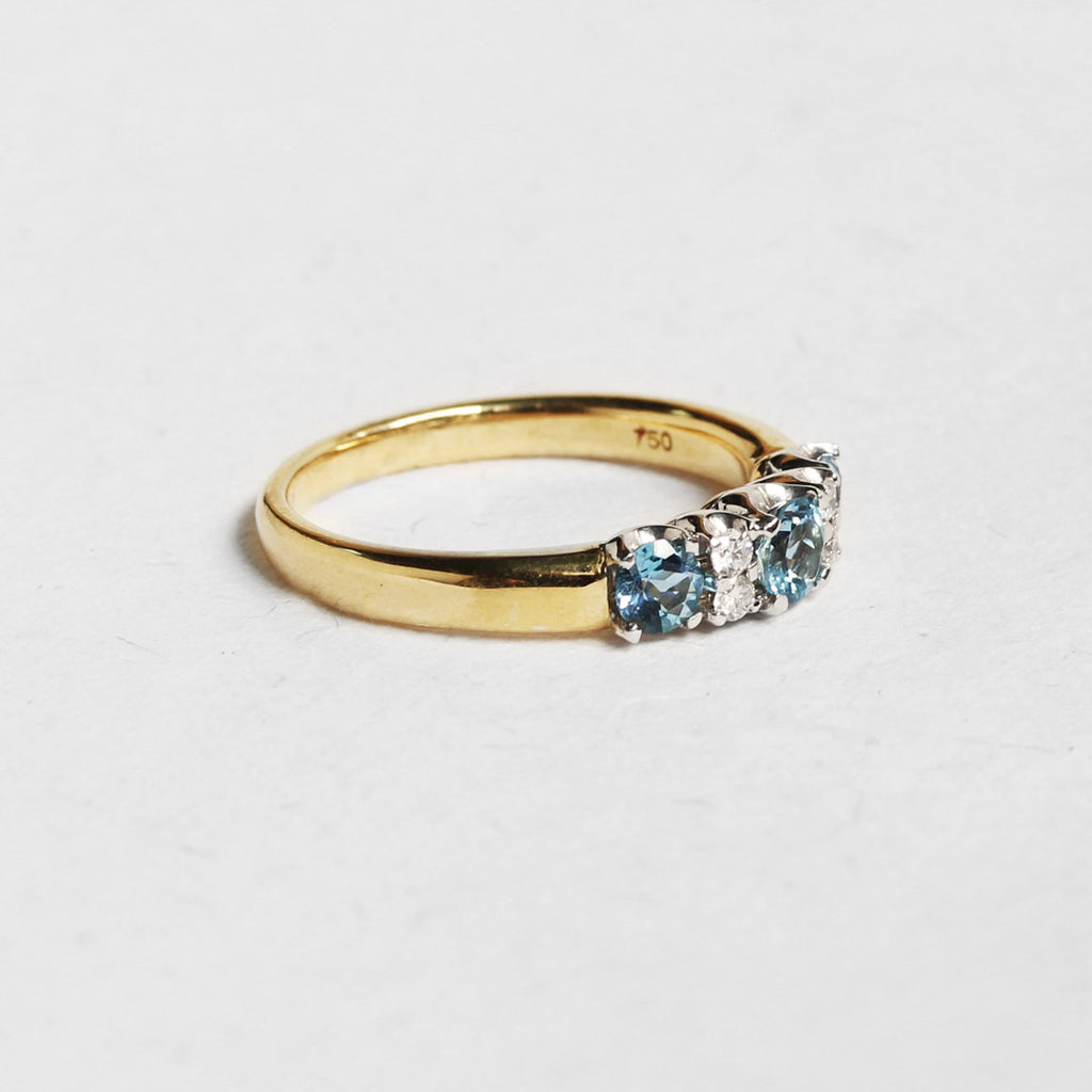 side view of yellow gold engagment ring set with white diamonds,  aquamarine gemstones. White background.