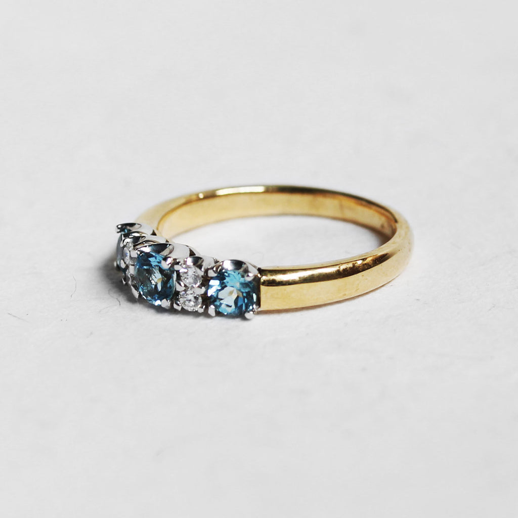 side view of yellow gold engagment ring set with white diamonds and aquamarine gemstones. White background.