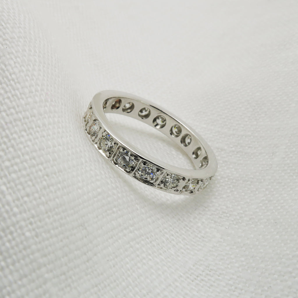 18ct white gold diamond set wedding band rests on an angle on white fabric.