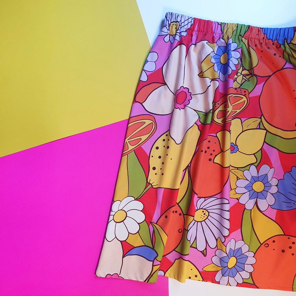 Ladies midi length citrus zesty skirt in tones of pink, orange, yellow, green, purple and white.