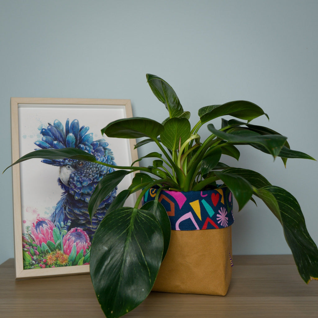 Paper pot planter in tan washable paper with canvas collar showcasing plant and artwork